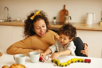 family childcare learning development fine motor skills concept caring young hispanic woman drinking coffee kitchen while handsome baby son sitting her playing with toy railway 344912 1933